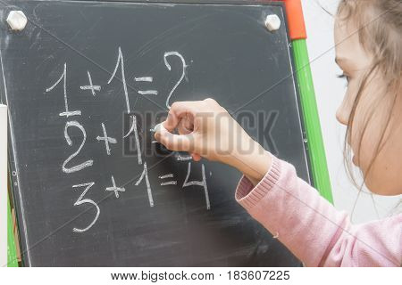 Girl At A Board Solves Examples On Mathematics. Training Of The Child.