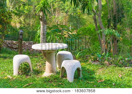 Garden seat of stone or stone table and benches in the garden and park outdoor