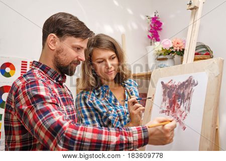 Teacher explains the principles of work with oil paints. A student girl closely follows the work. Courses of drawing for adults.