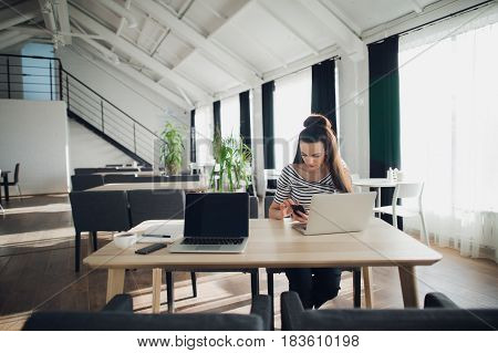 Adult attractive woman checking phone while sitting with a laptop at the table in a cafe