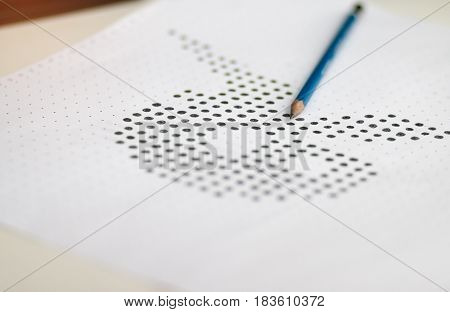test form or paper with answers bubbled in and pencil resting on the paper