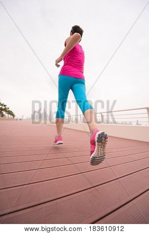 very active young beautiful woman busy running on the promenade along the ocean side with a big modern city in the background to keep up her fitness levels as much as possible