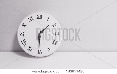 Closeup white clock for decorate show half past one o'clock or 1:30 p.m. on white wood desk and wallpaper textured background in black and white tone with copy space