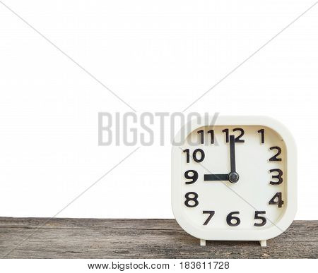 Closeup white clock for decorate in 9 o'clock on old brown wood desk isolated on white background with copy space