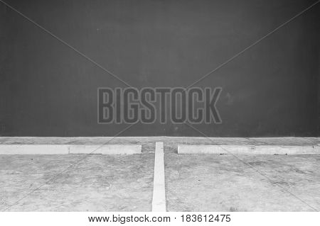 Closeup surface line slot for parking on cement floor with blurred dark gray cement wall in the garage textured background in black and white tone with copy space