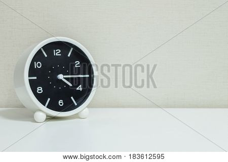Closeup black and white alarm clock for decorate show a quarter past four o'clock or 4:15 p.m.on white wood desk and cream wallpaper textured background with copy space