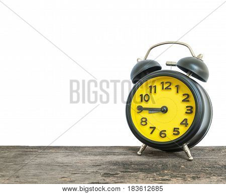 Closeup black and yellow alarm clock for decorate show a quarter to nine o'clock or 8:45 a.m. on old brown wood desk isolated on white background with copy space
