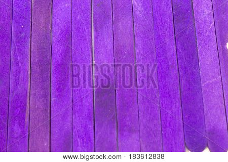 This is a photograph of Purple colored popsicle sticks background