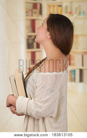 Young Pretty Woman holding a book and smiling.