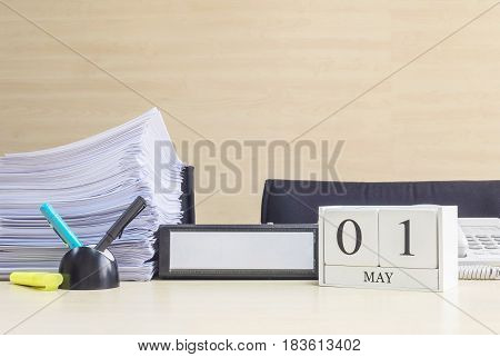 Closeup white wooden calendar with black 1 may word on blurred brown wood desk and wood wall textured background in office room view with copy space selective focus at the calendar
