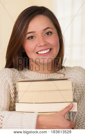 Woman holding pile of books, close up