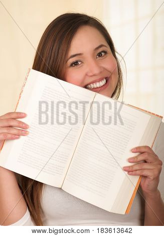 Young Pretty Woman Hiding Behind Open Book and smiling.