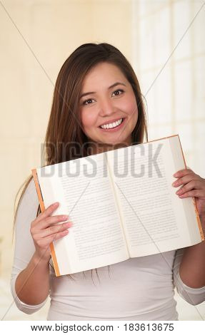 Young Pretty Woman holding an Open Book and smiling.