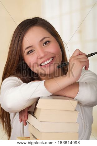 Beautiful woman resting over a pile of books and happy in the library