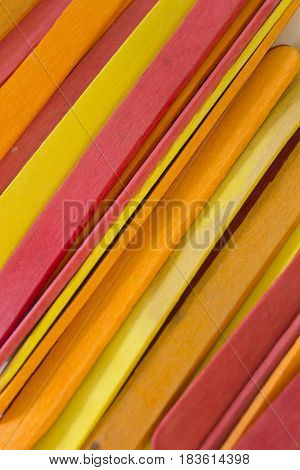 This is a photograph of Red, Yellow and Orange colored popsicle sticks background