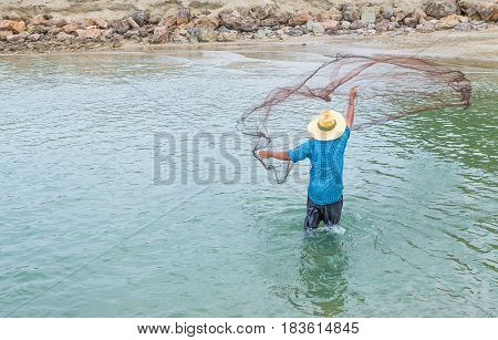 Men throw a net on the rive