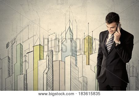 A young adult businessman standing in front of a wall with colorful drawings of buildings, charts, graphs, signs