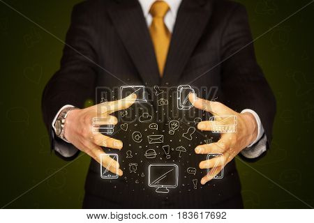 Businessman holding icons related to devices and communication