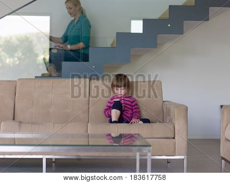 Portrait of cute little girl playing games on smartphone at home