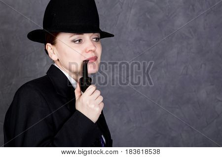 beautiful woman in manly style with smoking pipe on gray background, girl in man's suit and tie, white shirt and hat.