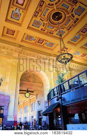 March 20, 2017 in Kansas City, MO:  Historical decorative train station with detailed architectural interior design with large chandeliers taken at the 100 year old Union Station where people can take Amtrak, dine, visit museums, and enjoy the historic bu