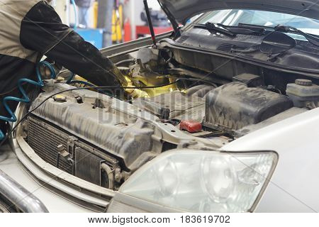 Worker works with a car in a car repair station