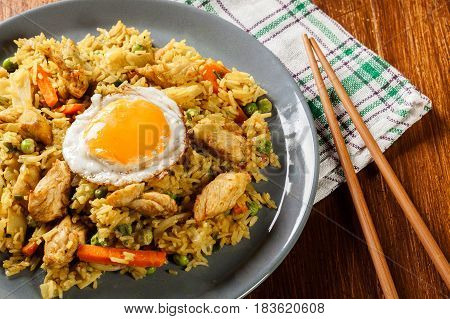Fried rice nasi goreng with chicken egg and vegetables on a plate. Indonesian cuisine. Top view