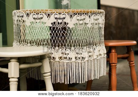 Lace tablecloth with fringe on the round table outdoos.