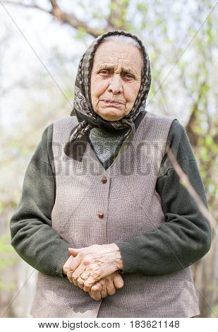 Portrait of a senior lady wearing a headscarf posing in the garden in springtime