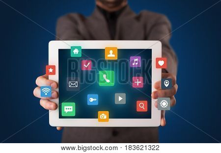 Businessman holding tablet with colorful applications