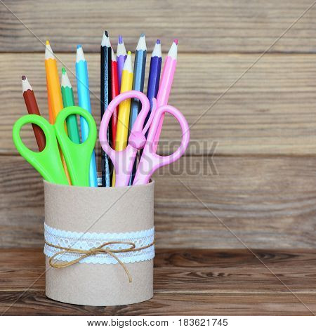 Colored pencils and scissors in a decorative tin can. Recycled tin can for storage of stationery isolated on wooden background. Closeup