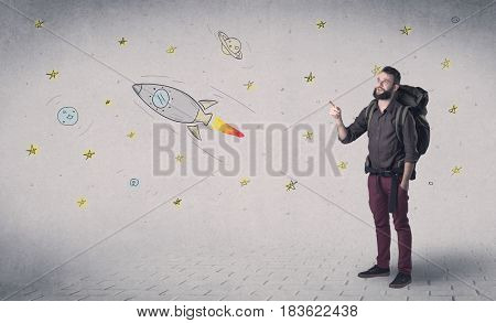 Handsome young man standing with a backpack with space related drawings in the background
