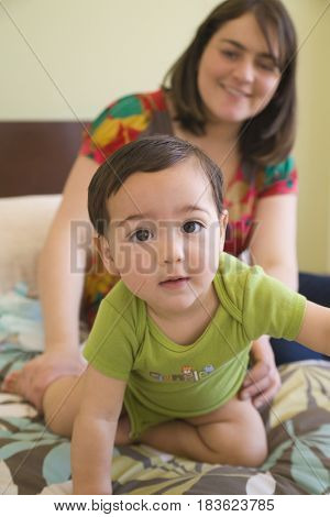 Hispanic mother watching son crawl on bed