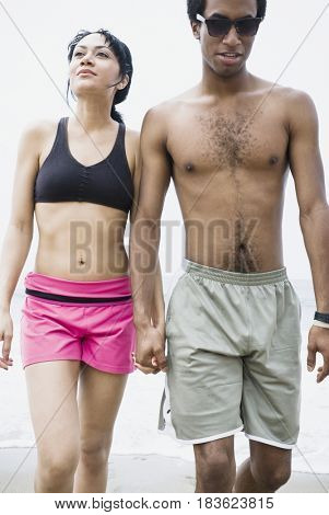Mixed race couple holding hands on beach