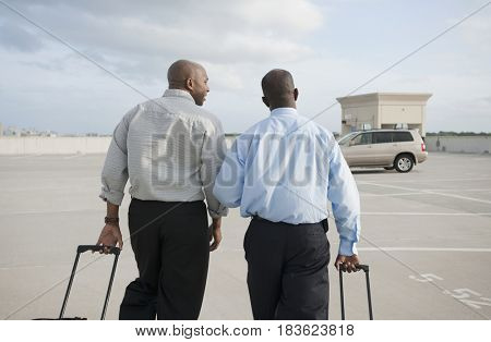 African businessmen pulling luggage in parking lot