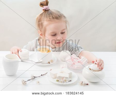 Little girl with sweets around her, ready for her teatime