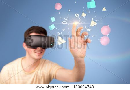 Young impressed man wearing virtual reality goggles with geometric shapes around his hand