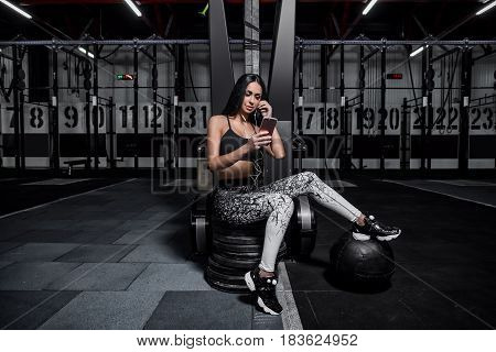 Attractive athletic girl listens to music from the phone in headphones. Sports girl resting after training. Fitness trainer rest between sets.