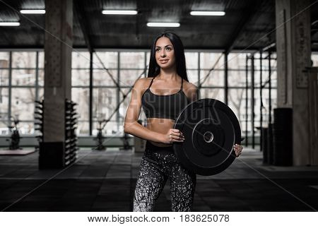 A sporty attractive girl posing with a sports equipment in the gym. The athlete holds the dumbbell with ease.