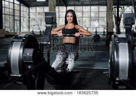 Powerful attractive muscular woman fitness trainer do workout on indoor rower at the gym