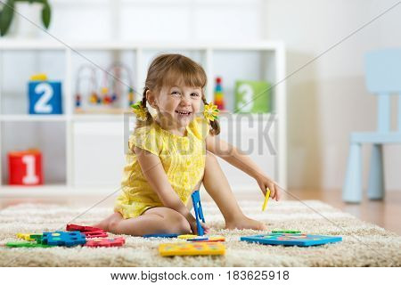 Child girl playing with sorter toy sitting on soft carpet at home