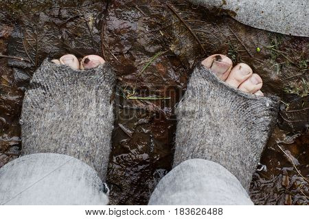 Bare feet in ragged woolen socks standing in mud and fallen leaves concept of poverty