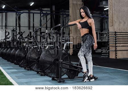 Young attractive woman using exercise bike at the gym. Fitness female using air bike for cardio workout at fitness gym.Sports brunette posing near a row of bicycles in the gym