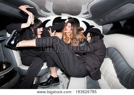 Two women and a man pull the hair and beat each other. Fight in the car. Horizontal indoors shot of stylish man and women having fun in a limousine together.