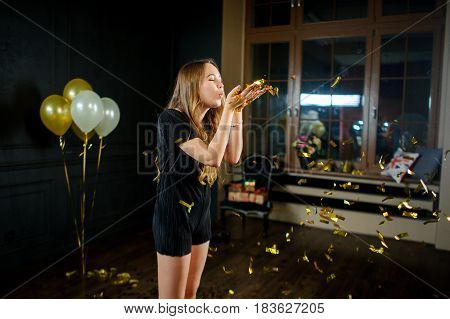 Beautiful young birthday girl after the end of a party. Girl blows off gold confetti from palms. She one in a make-up room. Flowers balloons gifts remind of a holiday.