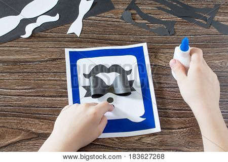 The Child Glues Together The Paper Parts. Greeting Card For Father's Day. Made By Own Hands. Childre