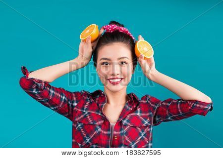 Healthy food. Smiling lovely pinup asian girl holding orange over blue background.