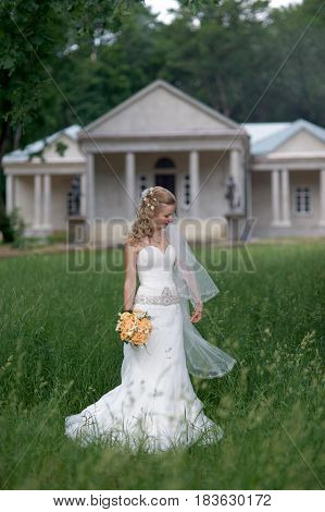 Portrait of Beautiful bride holding bouquet and posing outdoors