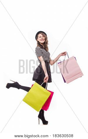 Full Length Side View Of Young Woman Walking With Shopping Bag Isolated Over White Background