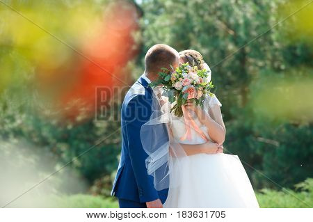 Kissing couple of newlyweds covering a person with a wedding bouquet